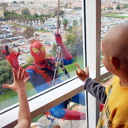 Window cleaners give some Purim entertainment at Shneider Children's Medical Center in Petah Tikvah.